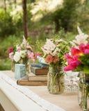 La tabla del jardín de la lectura puso afuera con las flores rosadas brillantes en floreros Imagen de archivo libre de regalías