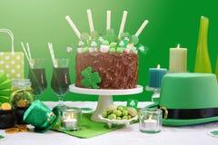 La tabla del partido del día del ` s de St Patrick con la torta de chocolate, el sombrero del duende y la lente señalan por medio Fotografía de archivo libre de regalías