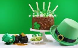 La tabla del partido del día del ` s de St Patrick con la torta de chocolate, el sombrero del duende y la lente señalan por medio Foto de archivo