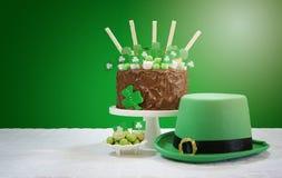 La tabla del partido del día del ` s de St Patrick con la torta de chocolate, el sombrero del duende y la lente señalan por medio Fotos de archivo libres de regalías