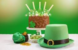 La tabla del partido del día del ` s de St Patrick con la torta de chocolate, el sombrero del duende y la lente señalan por medio Imagenes de archivo