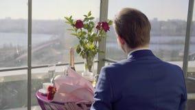 La tabla del restaurante en el tejado con el wiev del río que sorprende, hombre en traje se sienta en esta tabla con las rosas y  almacen de metraje de vídeo