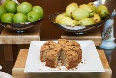 La tabla del servicio del abastecimiento con la fruta fresca y los pasteles se apelmaza Imagen de archivo libre de regalías