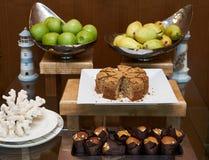 La tabla del servicio del abastecimiento con la fruta fresca y los pasteles se apelmaza Imagenes de archivo