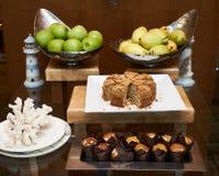 La tabla del servicio del abastecimiento con la fruta fresca y los pasteles se apelmaza Imagen de archivo