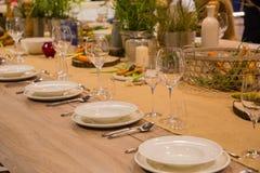 La tabla en el restaurante sirvió para varias personas con los vidrios y las placas imagen de archivo