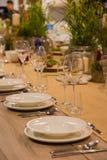 La tabla en el restaurante sirvió para varias personas con los vidrios y las placas imagenes de archivo