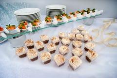La tabla festiva servida de la barra de caramelo con las magdalenas se eleva y el amor es muestra dulce Imagen de archivo libre de regalías
