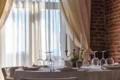 La tabla fijó con las velas en un restaurante lujoso con la pared de ladrillo Foto de archivo libre de regalías