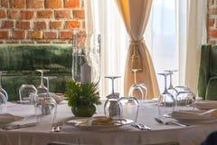 La tabla fijó con las velas en un restaurante lujoso con la pared de ladrillo Imagenes de archivo
