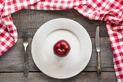 La tabla fijó con la manzana roja en la placa blanca con el cuchillo y la bifurcación con la servilleta a cuadros roja Fotografía de archivo