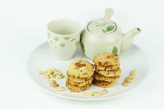 La tabla fijó para la merienda-cena con las galletas en el fondo blanco Fotografía de archivo