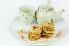 La tabla fijó para la merienda-cena con las galletas en el fondo blanco Imágenes de archivo libres de regalías