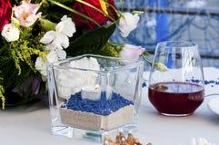 La tabla fijó por el mar con el vidrio del vino y de la vela Foto de archivo