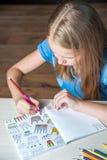 La tabla que se sienta de la muchacha bonita del retrato con el libro de colorear adulto dibujó a lápiz Fotografía de archivo