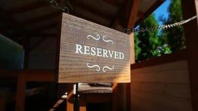 La tabla reservada de madera en las cadenas de acero, blanco imprimió letras en el tablero de la madera, tabla reservado almacen de metraje de vídeo