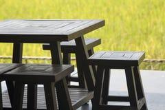 La tabla y las sillas de madera con el campo de hierba amarillo empañan el fondo Fotos de archivo libres de regalías