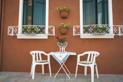 Tabla y sillas fuera de una casa, Burano, Italia imágenes de archivo libres de regalías
