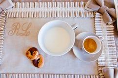 La table élégante a placé pour le petit déjeuner avec du lait, le café et des biscuits Photo libre de droits