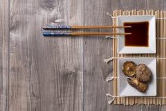 La table asiatique avec les baguettes, la sauce de soja et le shitake répand image stock