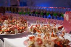 La table de banquet de restauration avec les casse-croûte de nourriture, les sandwichs, les gâteaux, les tasses et les plats cuit Image stock