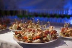 La table de banquet de restauration avec les casse-croûte de nourriture, les sandwichs, les gâteaux, les tasses et les plats cuit Photo stock