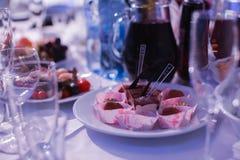 La table de banquet de restauration avec les casse-croûte de nourriture, les sandwichs, les gâteaux, les tasses et les plats cuit Photographie stock