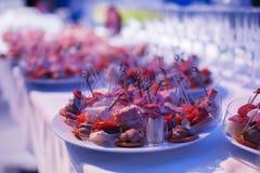 La table de banquet de restauration avec les casse-croûte de nourriture, les sandwichs, les gâteaux, les tasses et les plats cuit Images stock
