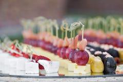La table de banquet de restauration avec les casse-croûte de nourriture, les sandwichs, les gâteaux, les tasses et les plats cuit Photo libre de droits