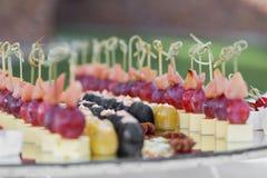 La table de banquet de restauration avec les casse-croûte de nourriture, les sandwichs, les gâteaux, les tasses et les plats cuit Photos stock