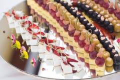 La table de banquet de restauration avec les casse-croûte de nourriture, les sandwichs, les gâteaux, les tasses et les plats cuit Photos libres de droits