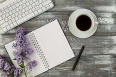 La table de bureau avec l'ordinateur, les approvisionnements, la tasse de café et la pivoine fleurit Fond en bois blanc Pause-caf photos libres de droits