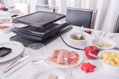 La table de dîner s'est préparée au raclette avec des amis avec la décoration Photographie stock libre de droits