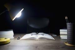 La table de lecture à la nuit, aux livres ouverts et aux verres a placé, Division de livre et lampes d'éclairage photos libres de droits