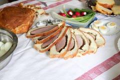 La table de Pâques avec des oeufs, le jambon en pâte, le pain fait maison, les radis et les jeunes cintrent photographie stock libre de droits