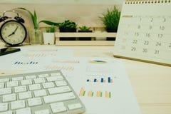 La table de travail avec le clavier, graphique d'infos, horloge et a l'endroit d'usines Images libres de droits