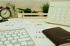 La table de travail avec le clavier, passeport, graphique d'infos, horloge et a le pl Images stock