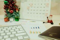 La table de travail avec le clavier, passeport, graphique et a le père noël, c Images libres de droits