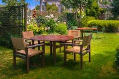 La table dinante a placé dans le jardin abondant photographie stock
