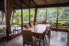 La table en bois dans la maison en verre, décoration de pièce avec du bois Photo stock