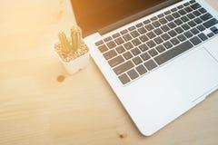 La table en bois de bureau avec l'ordinateur portable moderne et le cactus fleurissent sur le blanc Photos libres de droits