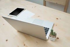 La table en bois de bureau avec l'ordinateur portable moderne et le cactus fleurissent sur le blanc Photos stock