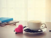 La table en bois de bureau avec la tasse de café de latte et le coeur rose forment Photo stock