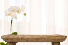 La table en bois de salle de bains sur le résumé a brouillé le fond avec la fleur d'orchidée photographie stock libre de droits