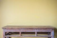 La table en bois de vintage supérieur vide et le ciment jaune murent le fond Photographie stock