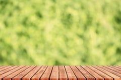 La table en bois supérieure vide a brouillé les feuilles vertes, tache floue d'abrégé sur vert Photos stock