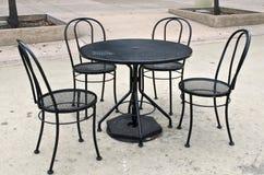 La table et la chaise noires ont placé en parc public Photos libres de droits
