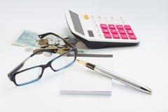 La table ou l'endroit blanche d'environnement de Workong avec des verres parquent la calculatrice et l'argent Images libres de droits