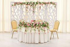 La table principale des nouveaux mariés, décorée d'une composition florale et d'une voûte dans des couleurs en pastel Photos stock