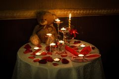 La table romantique de décoration a placé avec des bougies, des verres, des roses et l'ours de nounours ton chaud foncé image stock